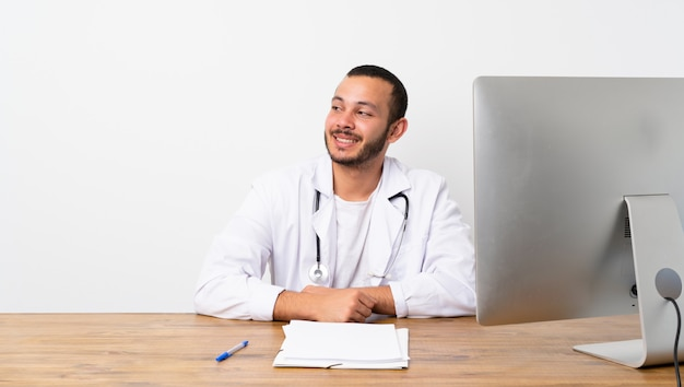 Doctor colombian man making doubts gesture looking side