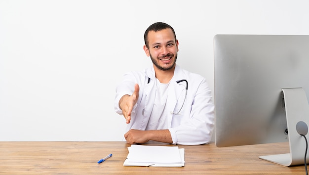 Doctor colombian man shaking hands for closing a good deal