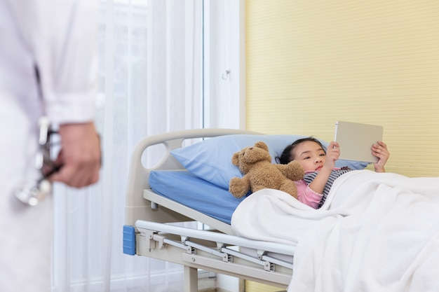 The doctor comes to check up a little girl who playing an ipad with a bear on the hospital bed.
