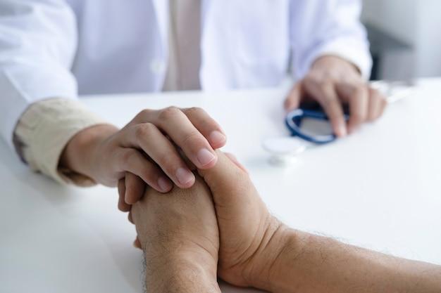 診察室で患者を慰める医師。