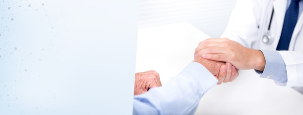 Doctor comforting a patient by holding his hand in the hospital - banner background