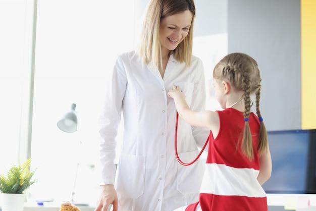 의사는 청진기를 들고 있는 어린 소녀와 의사 소통합니다. 의료 서비스 소아과 의사