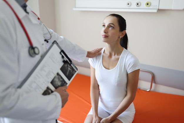 Врач общается с молодой пациенткой в концепции медицинских услуг больницы