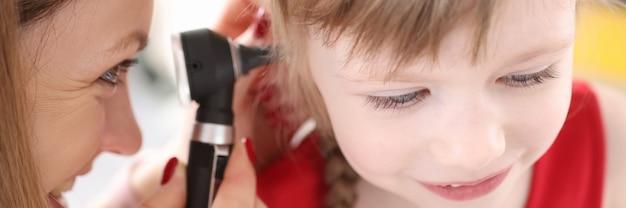 医者は少女の耳の健康診断を行います