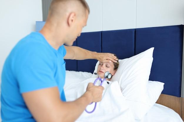 医者は休暇中にベッド中毒と発熱の病気の女性の健康診断を行います