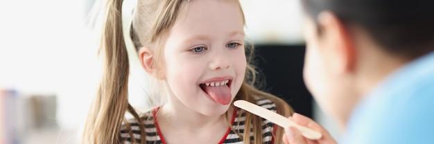 医者は少女の喉の身体検査を行います