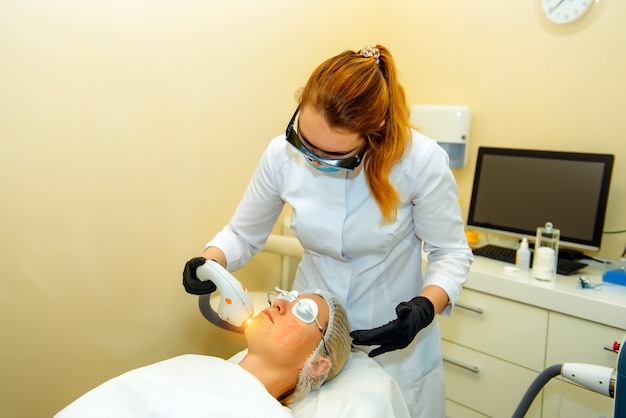 Doctor conducts procedure for rejuvenating facial skin with laser. woman receiving facial beauty treatment, removing pigmentation at clinic. intense pulsed light therapy. ipl. anti-aging procedures