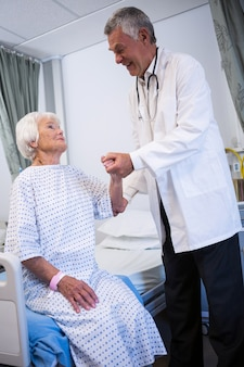 Doctor consoling senior patient in ward