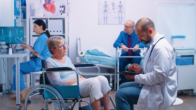 Doctor consultation in recovery clinic with elderly woman in wheelchair and senior man with disabilities holding onto a walking frame sitting in hospital bed. health care system, clinic patients at re