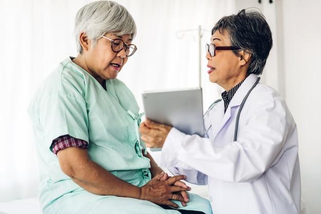 医師のコンサルティングと病院で年配の女性と情報を確認します。高齢者の女性はsick.healthcareと薬を持っています