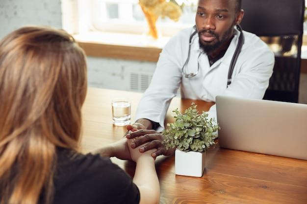 キャビネット内の女性患者のための医師のコンサルティング。患者との仕事中にアフリカ系アメリカ人の医師が、薬のレシピを説明します。流行中の健康と命を救うための毎日のハードワーク。