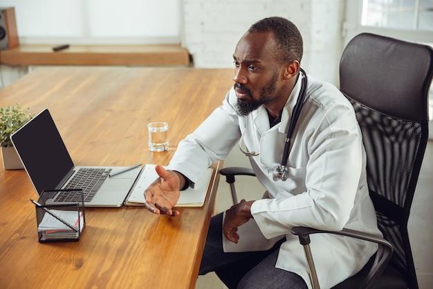 환자, 침착하고 쾌활한 의사 컨설팅. 아프리카 계 미국인 의사가 환자와 함께 일하는 동안 약물 조리법을 설명합니다. 전염병 중 건강과 생명을 구하기 위해 매일 노력합니다.