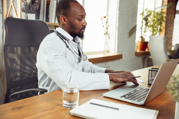 의사가 환자를위한 컨설팅, 랩톱 작업. 아프리카 계 미국인 의사가 환자와 함께 일하는 동안 약물 조리법을 설명합니다. 전염병 중 건강과 생명을 구하기 위해 매일 노력합니다.
