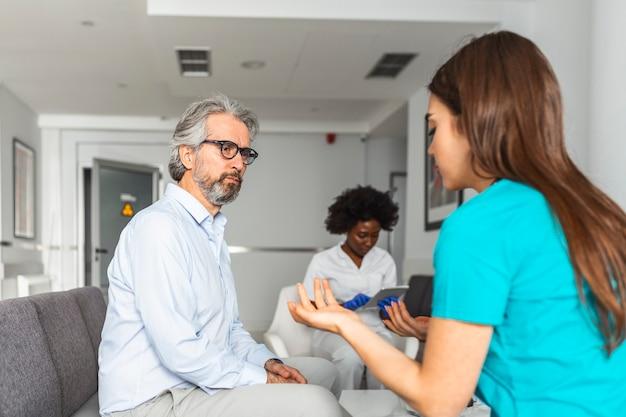 病院の待合室で患者に相談する医師