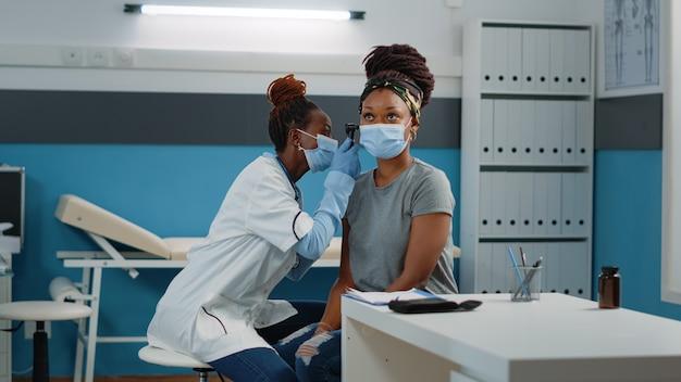Врач консультирует пациента с отоскопом для осмотра уха