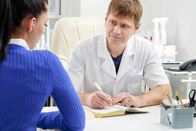 Doctor consulting young woman in his office