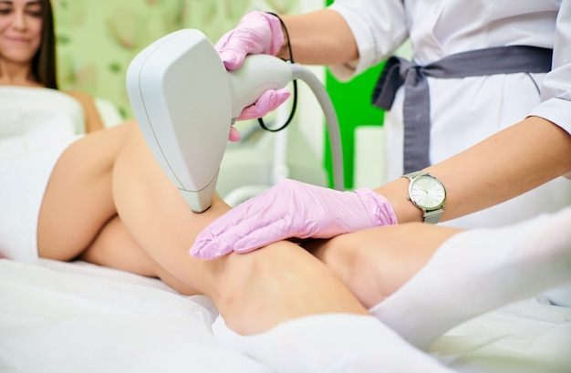 Doctor cosmetologist conducts the procedure of laser hair removal from the body of a girl