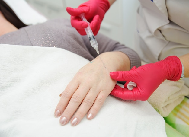 Doctor cosmetologist dermatologist conducts a session of mesotherapy or biorevitalization-removal of pigmentation on old women's hands. introduction of hyaluronic acid under the skin for rejuvenation.