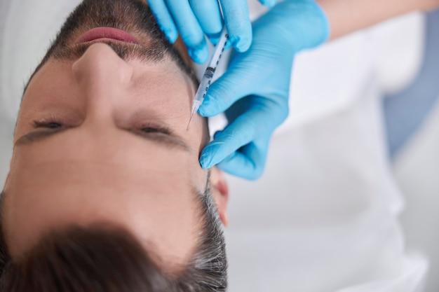 Врач косметолог делает инъекцию филлера для удаления гусиных лапок мужчине средних лет в красоте