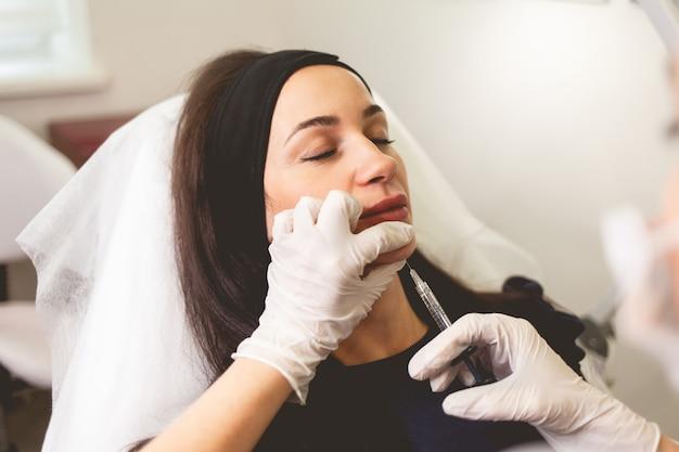 Врач косметолог делает укол подбородка пациенту