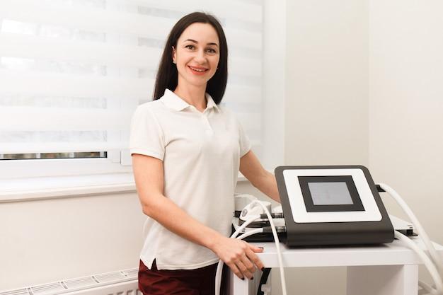 Врач косметолог держит в руках прибор для вакуумного антицеллюлитного массажа