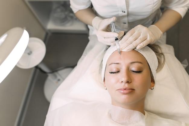 医師の美容師が女性患者の額に薬を注射します