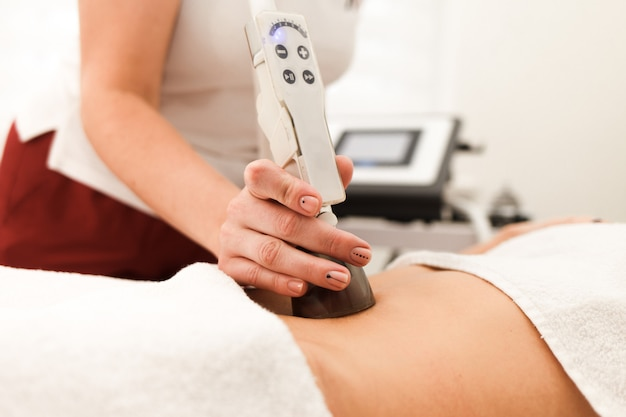Doctor cosmetologist makes anti-cellulite massage with the help of a vacuum device