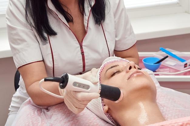 医師美容師は若い女性の顔の皮膚に器具マッサージを行います