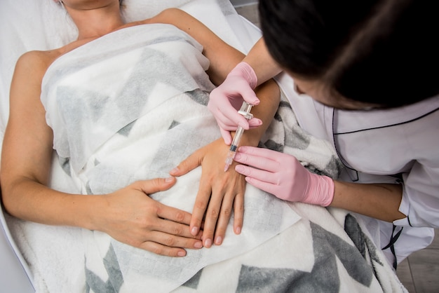 The doctor cosmetologist makes the arms injections procedure.