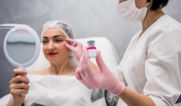 The doctor cosmetologist makes the facial injections procedure.