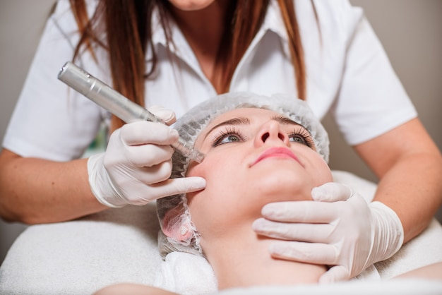 The doctor-cosmetologist makes a procedure of ultrasound cleaning of the facial skin