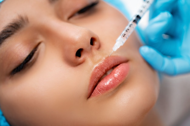 The doctor cosmetologist makes the rejuvenating facial injections procedure for tightening and smoothing wrinkles on the face skin of a women in a beauty salon. cosmetology skin care
