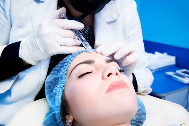 The doctor cosmetologist makes the rejuvenating facial injections procedure