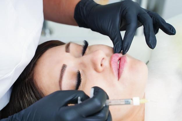 의사 미용사는 필러 주입으로 입술 확대 수술을 위해 환자를 준비합니다