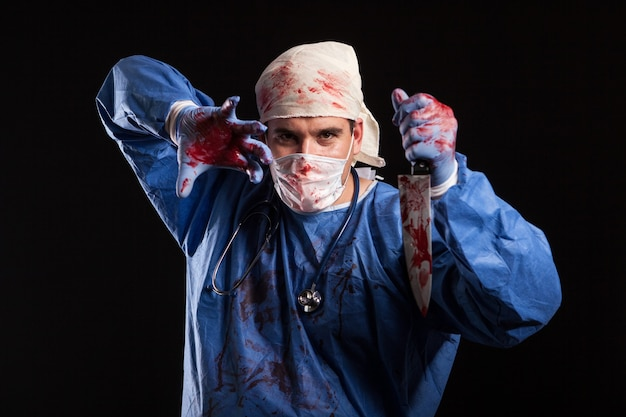 Doctor covered in blood with mask on his face for halloween in studio. portrait of a doctor looking like a scewball.