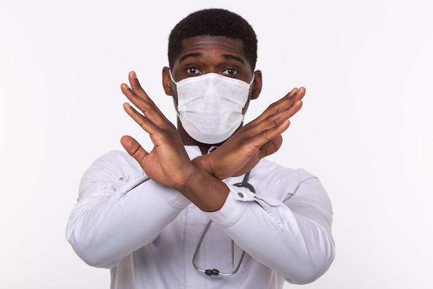医者は白い壁の胸に手を組んだ。彼は医療用マスクを着用しています。いいえまたはジェスチャーを停止します