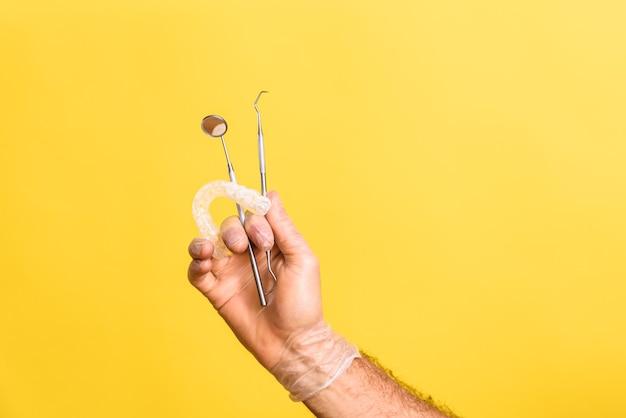 의사 치과 의사는 노란색 배경에 고립 된 다른 치과 도구 옆에 치과 정렬을 손에 보유하고 있습니다.