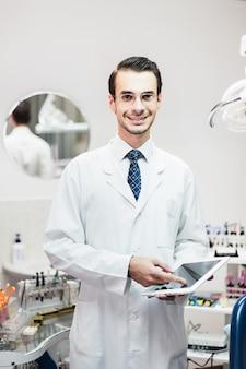 Доктор стоматолог в кабинете работает на планшете