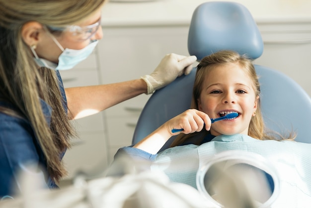Врач-стоматолог обучает ребенка чистить зубы.