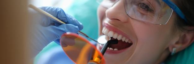 Врач-стоматолог лечит зубы с помощью светодиодной лампы для отверждения в клинике крупным планом