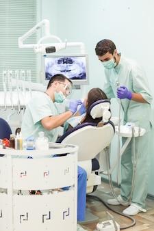 アシスタントと歯科医は歯科医院で働いています。