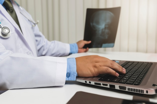 Doctor diagnose and analyze on x-ray film of patient.