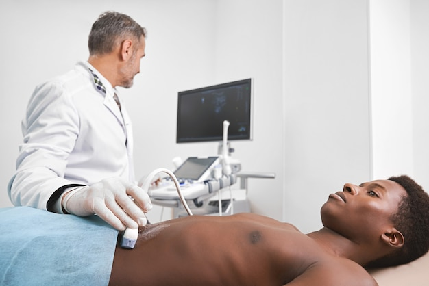 Doctor diagnosing belly of man with ultrasound probe.