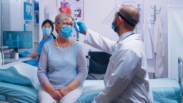 医師が患者情報を看護師に口述し、彼女はそれをpcに書き込みます。相談のために保護具を着用したマスクと医療従事者を身に着けている年配の老婆。