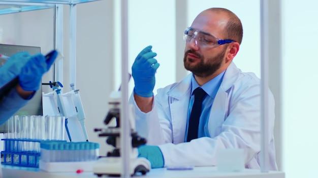 現代の設備の整った実験室で試験管を調べてウイルス結果情報を看護するように指示する医師。 covid19に対するハイテク研究診断を使用してワクチンの進化を調べる医師