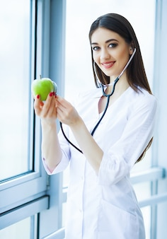 Doctor dietitian holding in hands fresh green apple and smiles.