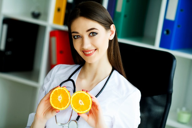 Doctor dietologist holds in the fresh orange hands. healthy nutrition. fresh vegetables and fruits on the table. happy doctor in the light room. high resolution