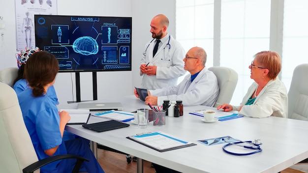 Врач обсуждает волну испарения в наушниках с датчиками. монитор показывает современное исследование мозга, в то время как группа ученых настраивает устройство, работая в конференц-зале больницы.