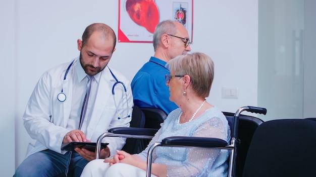 Врач обсуждает диагноз и восстановительное лечение с пожилой женщиной-инвалидом в инвалидной коляске. старик в зоне ожидания больницы. медик в стетоскопе и белом халате.