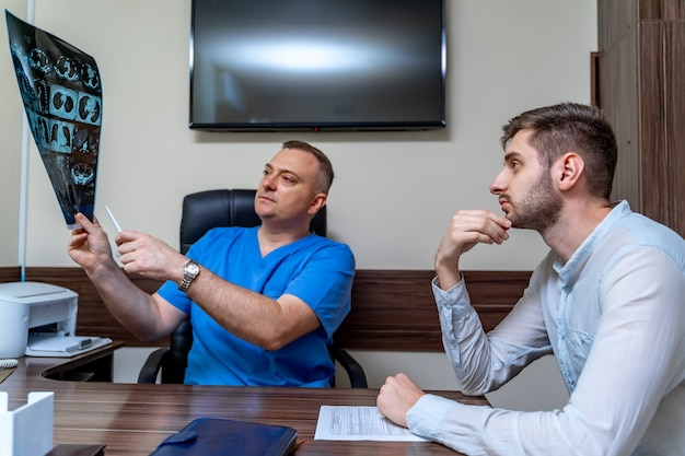 Doctor discussing diagnosis of x-ray image with male patient sitting in office.